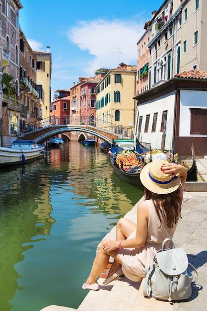 Красивая девушка в шляпе сидит возле канала в венеции, италия Premium Фотографии