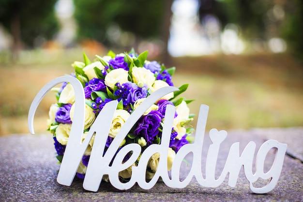 単語の結婚式と舗装の上に横たわるブライダルブーケ Premium写真