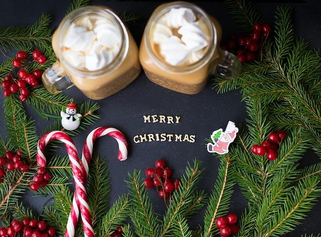 木の枝と黒い表面にマシュマロとキャンディーとココア。 Premium写真