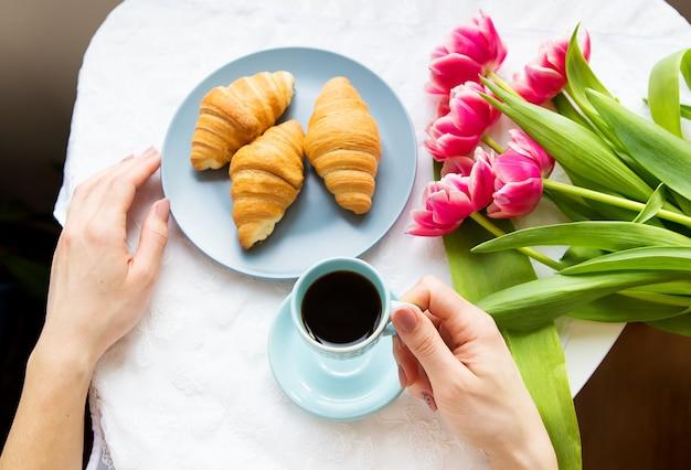 クロワッサン、コーヒー、ピンクのチューリップの花束 Premium写真