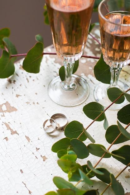 Эвкалиптовые ветки с бокалами розового вина и обручальными кольцами Premium Фотографии
