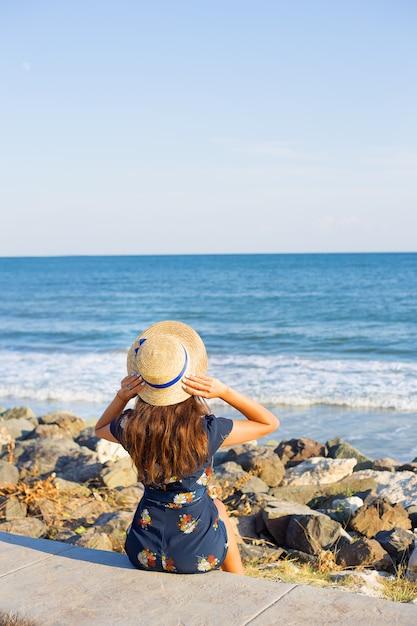 Красивая девушка в шляпе сидит возле моря на камнях Premium Фотографии