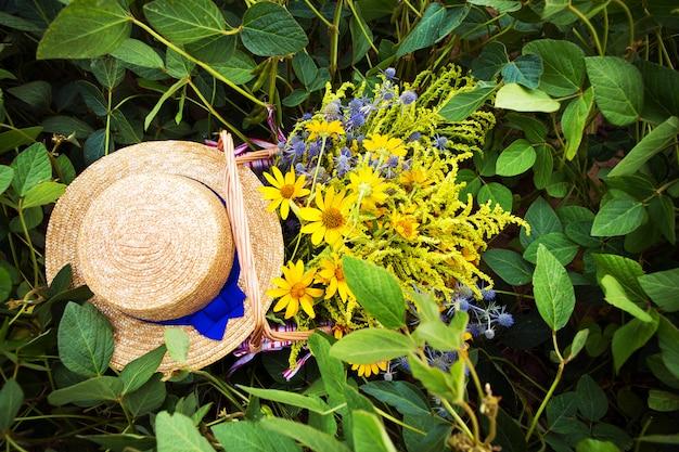 麦わら帽子と花のバスケットは草の上に立つクローズアップ Premium写真