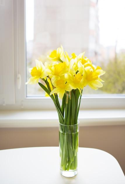 白い木製のテーブルに明るい黄色の水仙の花束 Premium写真