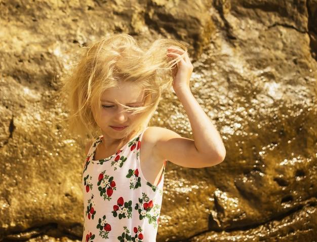 風がブロンドの女の子の髪をしている Premium写真