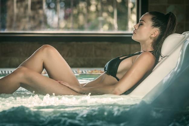 プールでスパプロシージャを楽しんでいる女性 Premium写真