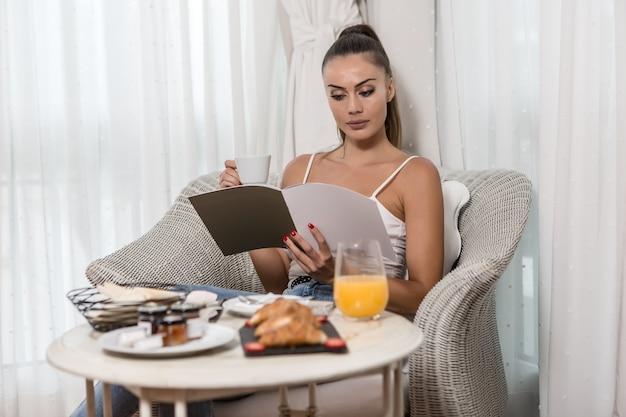 Женщина читает журнал во время завтрака Premium Фотографии