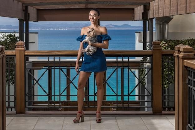 テラスに立っている小さな犬とスリムな女性 Premium写真