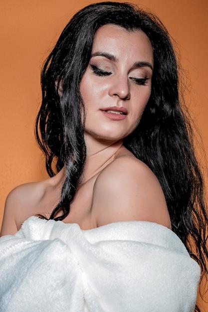長い巻き毛の美しいブルネットの少女の肖像画 Premium写真