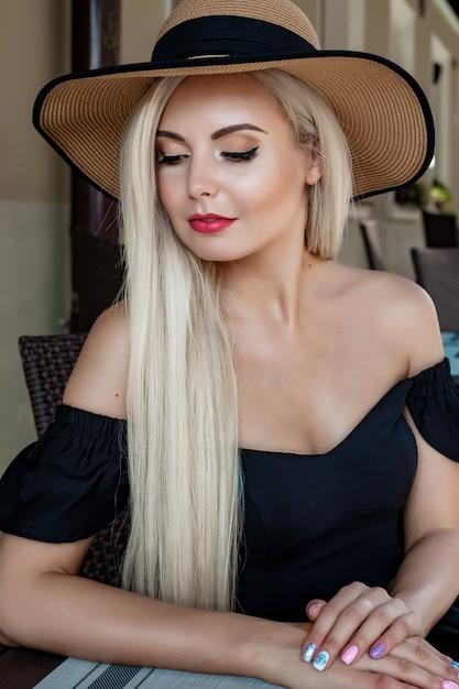 エレガントな麦わら帽子とテーブルのカフェに座っているドレスで優雅な女性のファッション性の高い肖像画 Premium写真