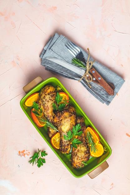 オレンジとローズマリーの緑の皿に焼きチキンドラムスティック Premium写真