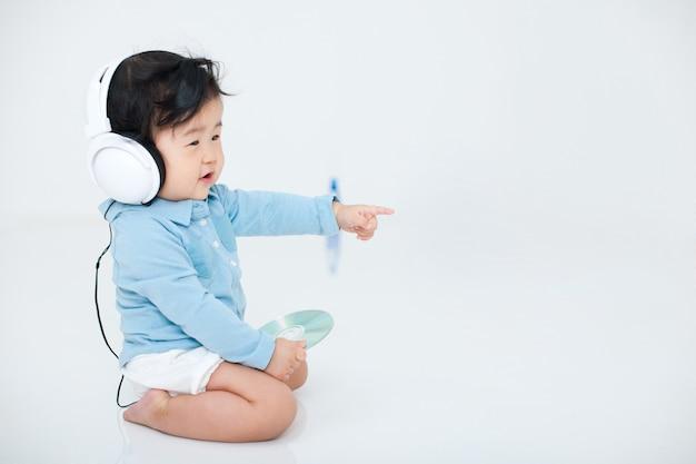 赤ちゃんは白で彼のヘッドフォンで喜んで遊んでいます。 Premium写真