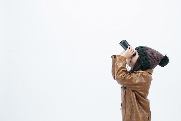 白い背景では、子供は双眼鏡のどこかを見ています。 Premium写真