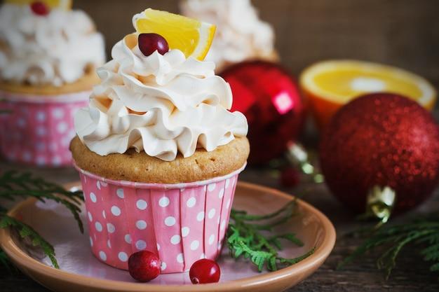 Рождественские кексы с взбитыми сливками и клюквой, апельсин. праздничная еда десерт. Premium Фотографии