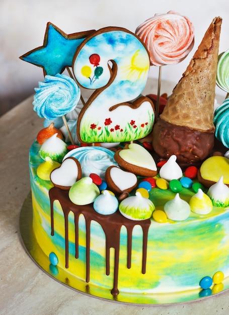 木製のメレンゲと白い表面上の子供のモダンなケーキ虹色 Premium写真