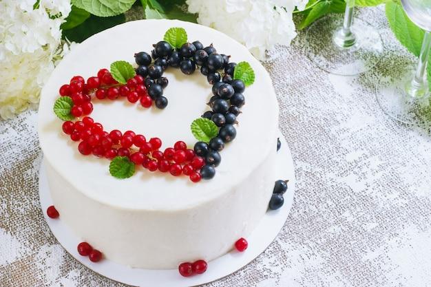 白い表面に、バレンタインの日、ハートの形の果実と丸い白いケーキ。メニューまたは菓子カタログの画像。上面図 Premium写真