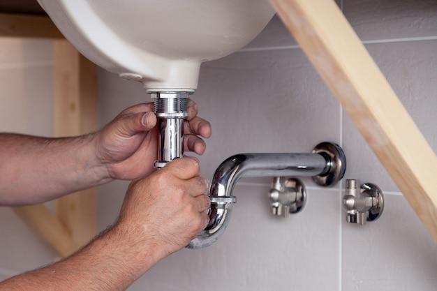 青いデニムのユニフォーム、オーバーオール、タイルの壁とバスルームのシンクを修正でクローズアップ男性配管工。専門の配管修理サービス、設置用水道管、人が取り付けた下水管 Premium写真