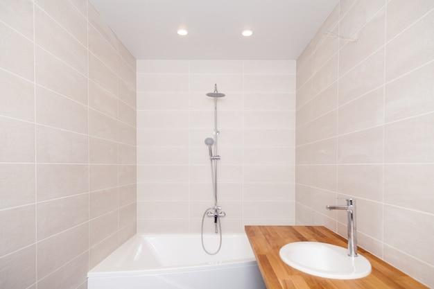 空の新しいバスルームには、ベージュのセラミックの長方形のタイル、大きなバスタブ、シルバーのシャワー、水道水、セラミックのシンクが付いた木製のワークトップがあります。バスルームの修理、アパートの改修、ホテル Premium写真