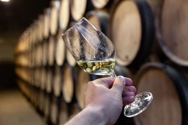 背景木製オーク樽に白ワインのグラスとクローズアップ手は、ワイナリーの古いセラー、ヴォールトの順序でまっすぐな行に積み上げられました。 Premium写真