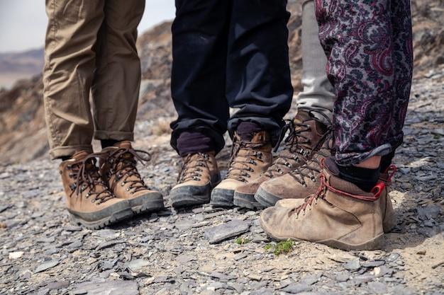 Туристические ноги вместе в коричневых походных ботинках с кружевами на скалистом утесе Premium Фотографии