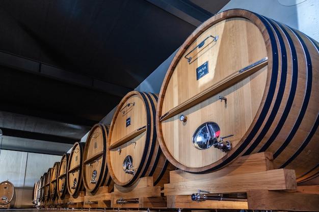 木樽、熟成、発酵プロセス、モダンなセラーに保管、チェスの床 Premium写真