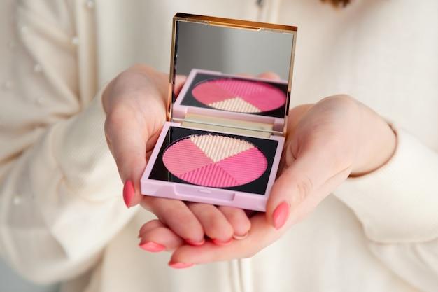 鏡で修正彫刻パレットピンク赤面を保持しているマニキュアで女性の手をクローズアップ。 Premium写真
