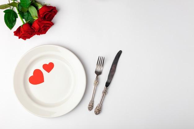 エレガントなテーブルセッティングと赤いバラ Premium写真