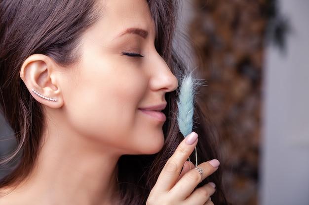 Крупным планом красивая брюнетка девушка с длинными волосами в современных серебряных ювелирных серьгах, кольцах, браслете, цепочке, ожерелье. Premium Фотографии