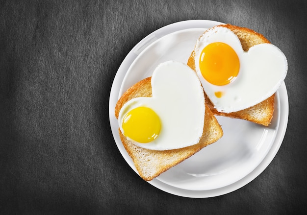 Два жареных яйца в форме сердца и жареные тосты Premium Фотографии