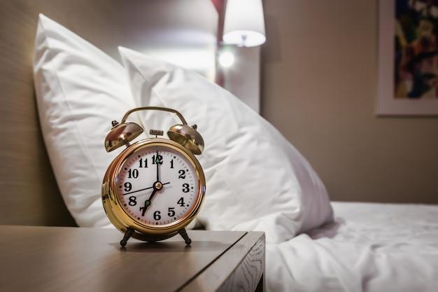 目覚まし時計はベッドサイドテーブルの上に立つ Premium写真