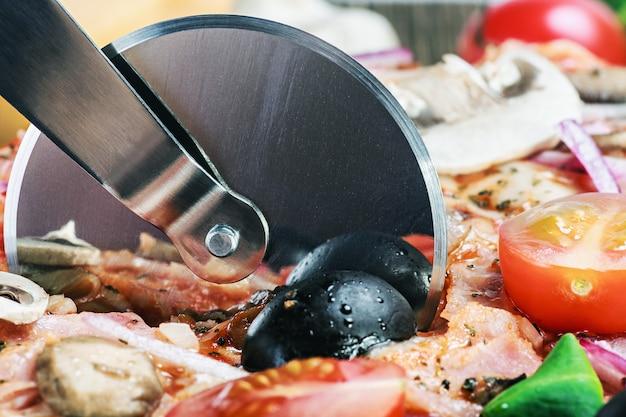 Резак режет свежую пиццу с грибами Premium Фотографии