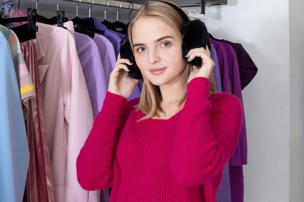 ピンクのセーターとふわふわの黒いイヤーマフを身に着けている店の若いおしゃれな女性。 Premium写真