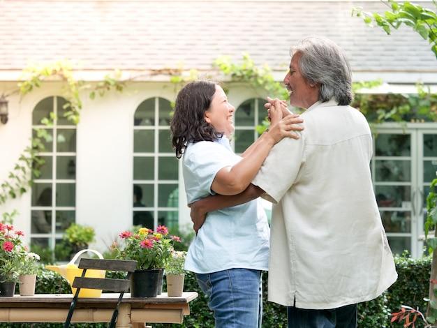 家庭庭で一緒に笑っているシニアカップル。 Premium写真
