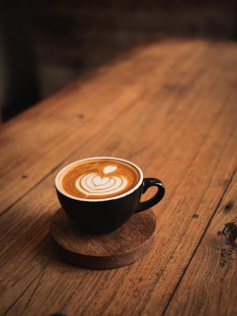 カフェの木の机の上のコーヒーカフェラテ Premium写真