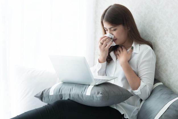 女性が熱を帯びているので、彼女は寝室でラップトップを使用している間くしゃみをしています。 Premium写真