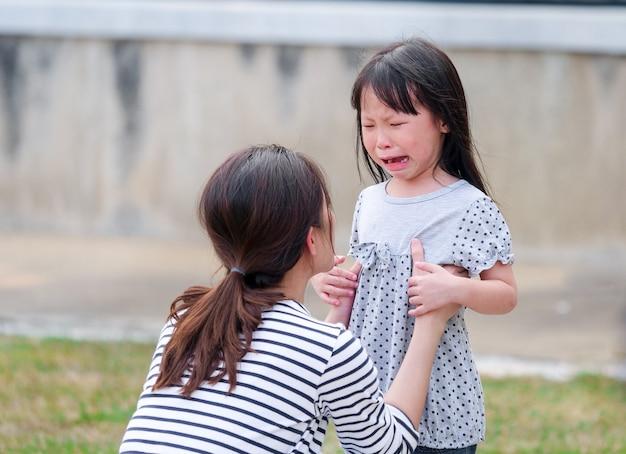 彼女の母親の腕の中で泣いている小さな女の子の顔を閉じます。 Premium写真
