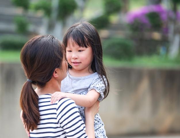 彼女の母親の腕の中で幸せな女の子の顔を閉じます。 Premium写真