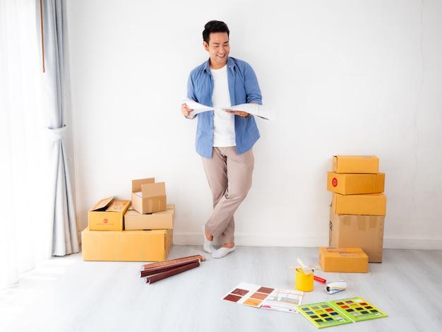 Азиатский мужчина дизайн и думать, чтобы украсить дом Premium Фотографии