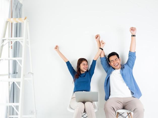 アジア人男性と女性の白い背景の上のビジネスのためのラップトップコンピューターと話しています。 Premium写真