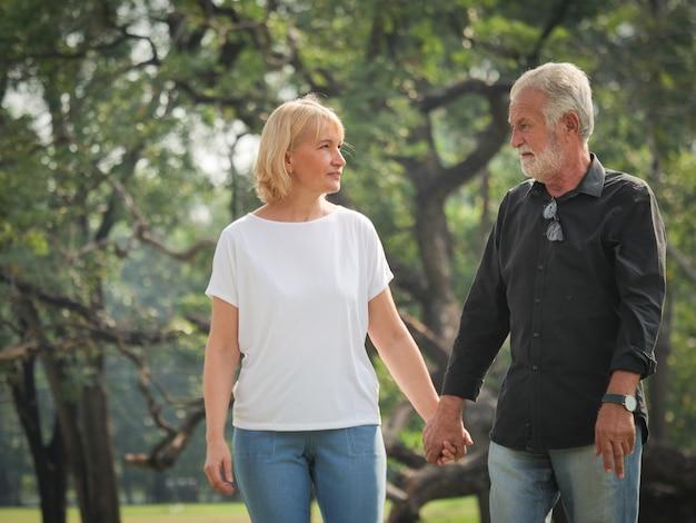 Два счастливых пенсионера на пенсию мужчина и женщина гуляют и разговаривают в парке Premium Фотографии