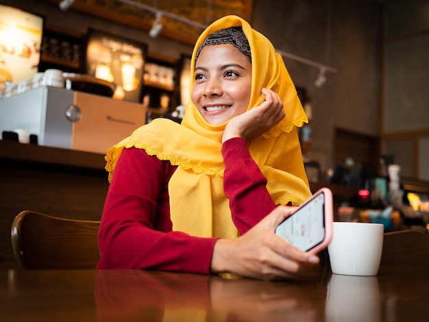 コーヒーショップで若いイスラム教徒の女性の肖像画 Premium写真