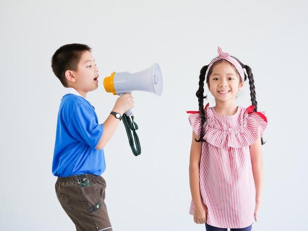 アジアのかわいい男の子とメガホン歌を持つ少女 Premium写真