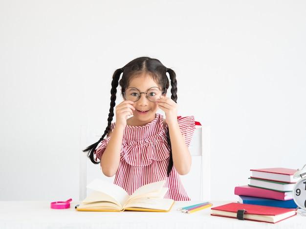 机の上の本とアジアのかわいい女の子 Premium写真