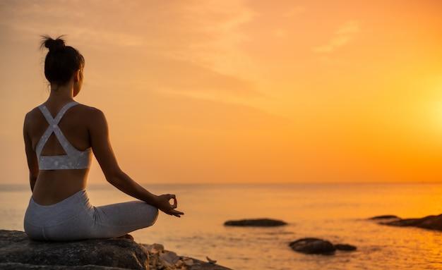 Азиатская девушка занимается йогой на пляже восход утреннего дня Premium Фотографии