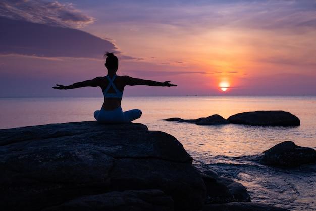 アジアの女の子がビーチでヨガを練習します。日の出の朝の日 Premium写真