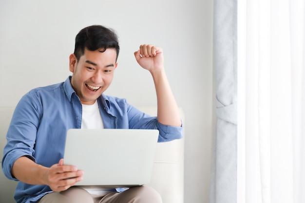 Азиатский красавец работает с ноутбуком в гостиной, счастливые и улыбающиеся лица Premium Фотографии