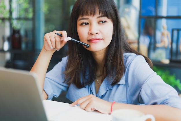ラップトップを使用して、コーヒーを飲みながら青いシャツを着てアジアの美しい女性 Premium写真
