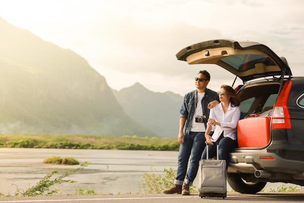 アジアカップルビンテージカメラと車の後ろに座っている女性を持つ男は、車の道旅行と休日に山と湖に旅行します。 Premium写真