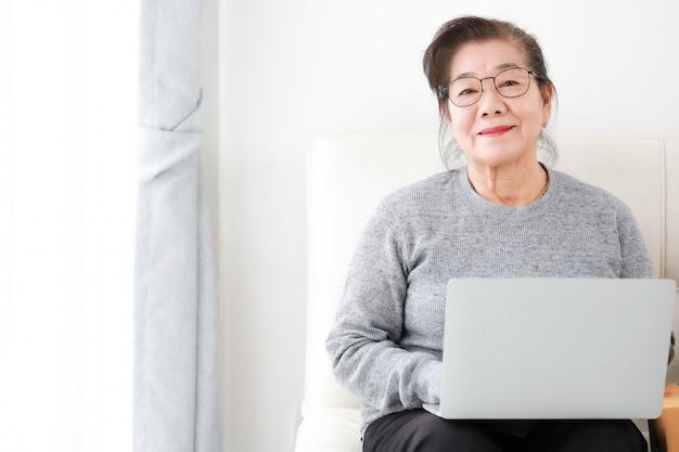 Азиатская старшая женщина на пенсию, используя портативный компьютер в гостиной Premium Фотографии