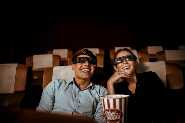 カップルは、ポップコーンの笑顔と幸せそうな顔で劇場で映画を見る Premium写真